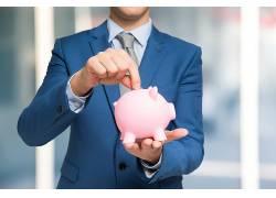 手拿粉色小猪储钱罐图片