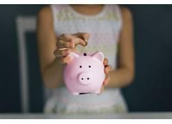 手拿粉色小猪存钱罐图片