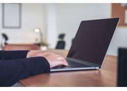 手按笔记本电脑键盘的人