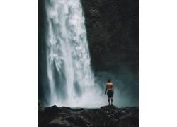 站在瀑布下的年轻人