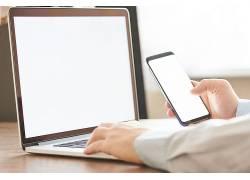 人手按笔记本电脑键盘手拿手机
