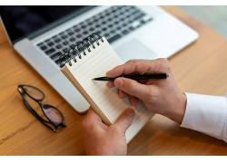 办公眼镜笔记本电脑手拿笔记事